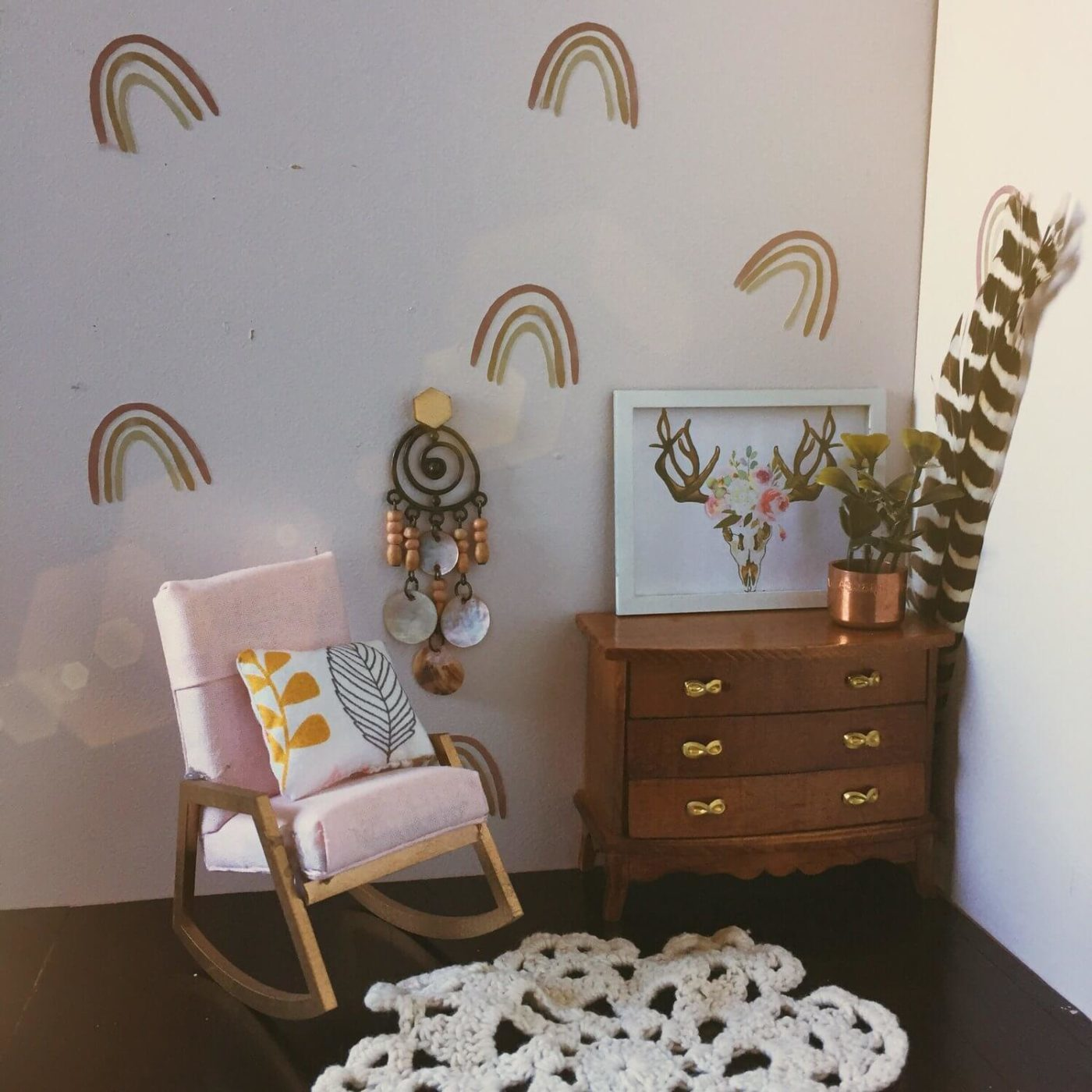 A close up of mini rainbow wall decals in a doll's house.
