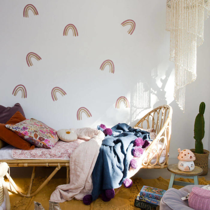 Medium dusty rainbow wall decals as home decor in a boho style kid's bedroom.