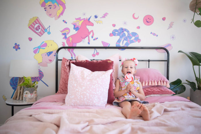 Happy girl on bed with pink wall decals in the background.