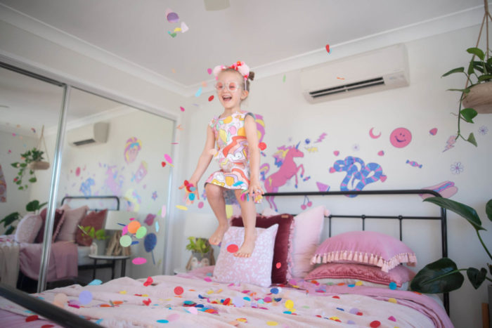 Happy girl jumping on pink bed with wall decals in the background.