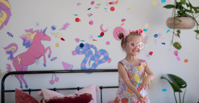 Stylish child throwing confetti with colourful wall decals in the background.