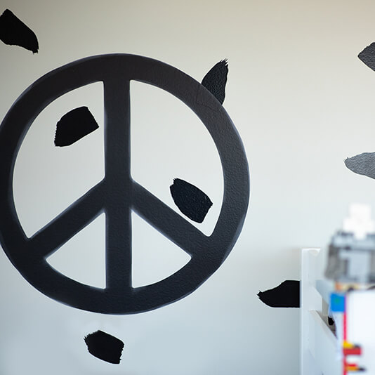 Monochrome peace symbol removable wall decal in a boy's bedroom.